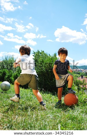 Two little kids with basketball and football - stock photo