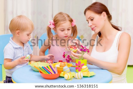 Two little kids with young teacher paint Easter eggs, art lesson, interacting children in daycare, Christian holiday concept - stock photo