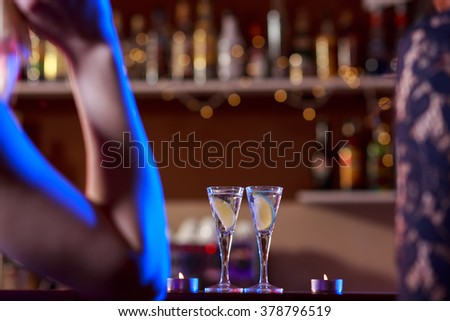 Two little liqueur glasses on bar in night club