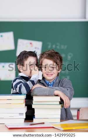 Two little male students having a gossip at the classroom - stock photo