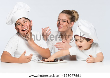 Two little monsters playing with chocolate cake and messing with dessert dish having fun and smiling - stock photo