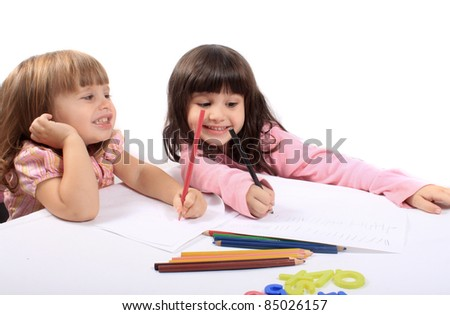 Two little preschool girls drawing with colorful pencil crayons - stock photo