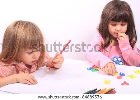 Two little preschool girls, one drawing with pencil the other playing with letters - stock photo
