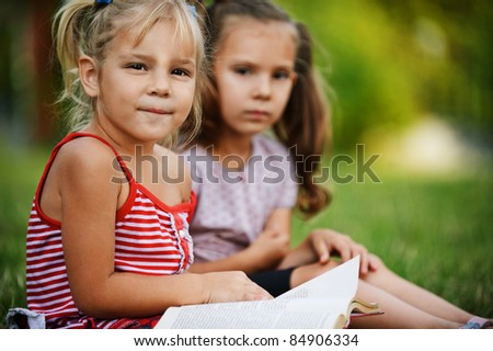 Two little pretty girls reading book at summer green park. - stock photo