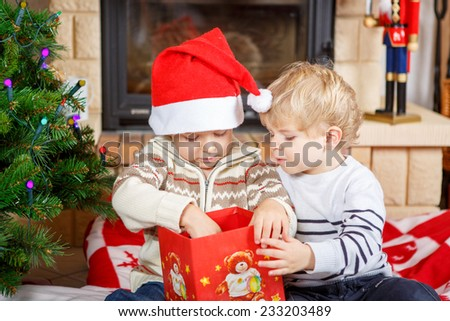 Two little sibling boys being happy about christmas presents, indoor with traditional decoration and fireplace. Family celebrating holiday. - stock photo