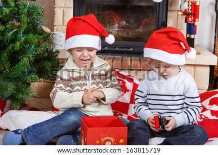 Two little sibling boys fighting about christmas present, indoor with christmas decoration. One boy crying. - stock photo