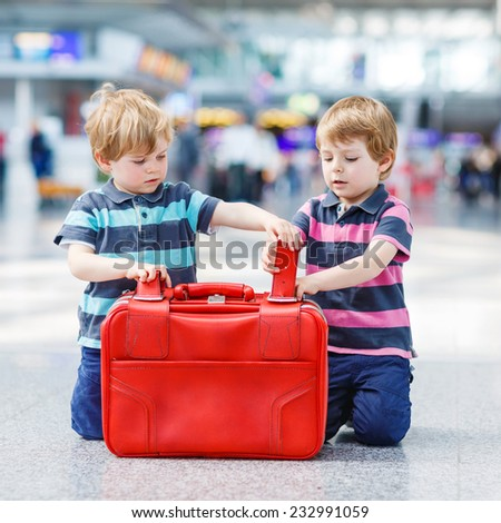 Two little sibling boys having fun and going on vacations trip with suitcase at airport, indoors. Square format.