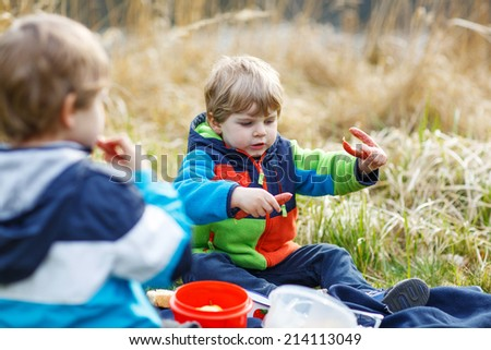 Two little sibling boys having picnic near forest lake, nature on cold spring or autumn day.
