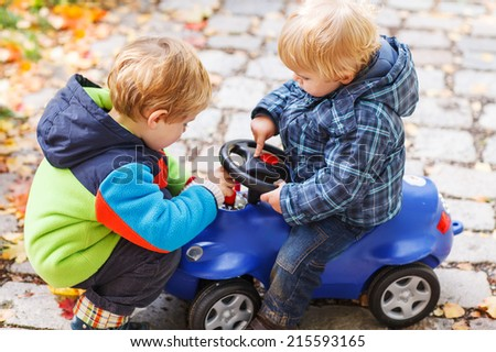 Two little sibling children playing with toy car on autumn day. Having fun together. - stock photo