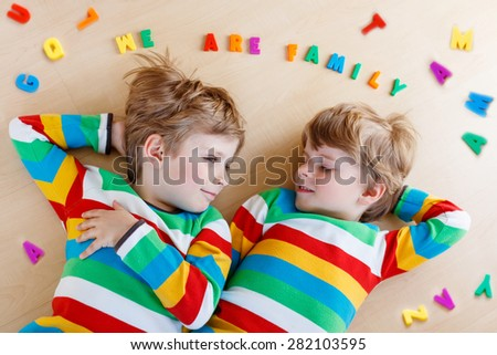 Two little sibling kid boys having fun together, indoors. Blond twins o in colorful shirts laughing and smiling. Family concept. - stock photo