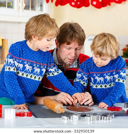 Two little siblings and father baking gingerbread cookies. Happy siblings, children in blue xmas pullovers. Kitchen decorated for Christmas. Family, holiday, kids lifestyle concept. - stock photo