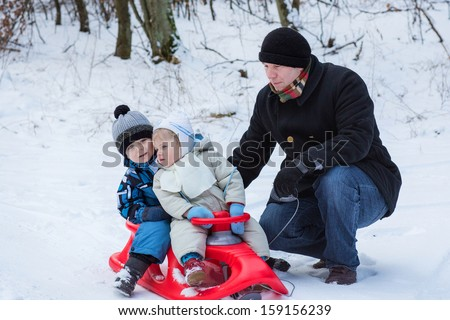 Two little siblings and their father having fun on sledge on winter snow day