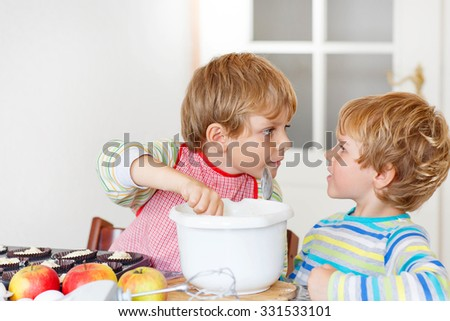 Two little siblings baking apple cake in domestic kitchen. Kid boys having fun with working with mixer, eggs and fruits. Children tasting dough