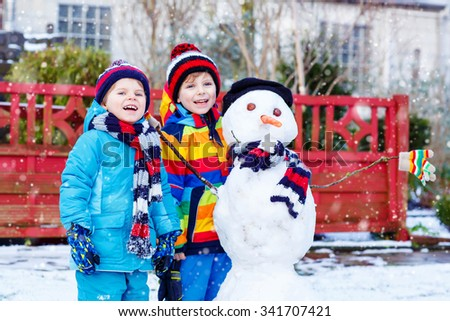 Two little siblings boys making a snowman. Kids playing and having fun with snow, outdoors  on cold day. Active outdoors leisure with children in winter. - stock photo