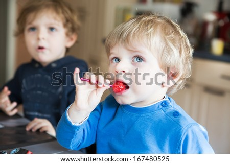 Two little siblings boys watching tv and eating candy indoor. Selective focus on one boy. - stock photo