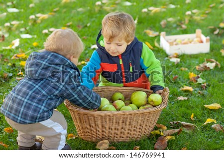 Two little siblings in autumn garden with basket full of apples - stock photo