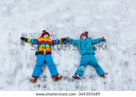 Two little siblings kid boys in colorful winter clothes making snow angel, laying down on snow. Active outdoors leisure with children in winter. Happy brothers with warm hat,  gloves, winter fashion - stock photo