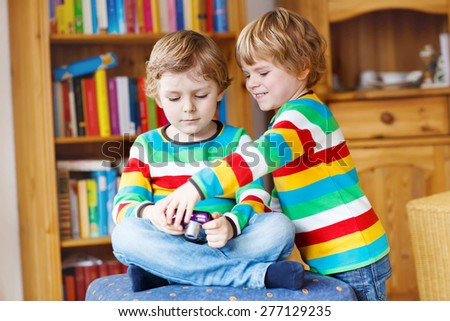 Two little siblings kid boys making photos with photocamera, indoors. Children wearing colorful shirt. Lifestyle in a daycare or at home. - stock photo