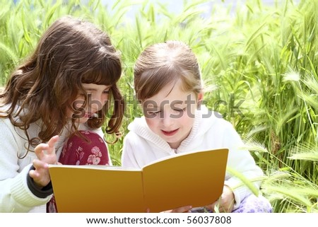 two little sister girls reading book spikes garden - stock photo