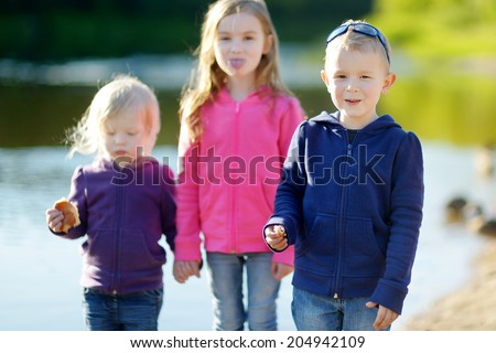 Two little sisters and their brother eating buns, laughing and joking by a river at sunny autumn day - stock photo