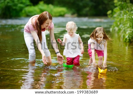 Two little sisters and their mom playing with paper boats in a river