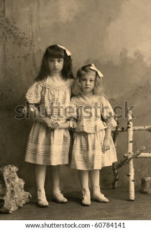 Two little sisters are looking at camera with identical frocks, hair bows and shoes. - stock photo