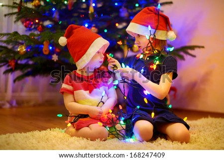 Two little sisters decorating Christmas tree - stock photo