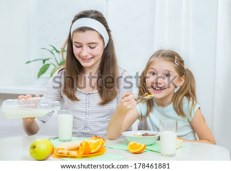 Two little sisters eating muesli with milk and fresh fruits  - stock photo
