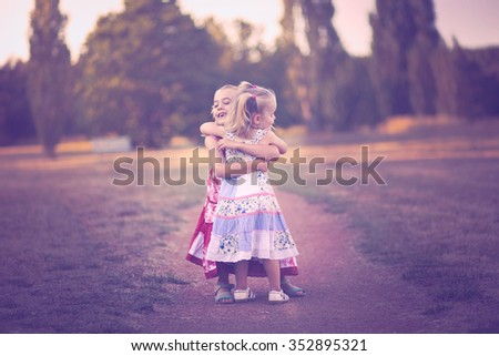 Two little sisters embracing - stock photo