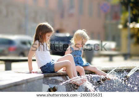 Two little sisters having fun in a city fountain at the hot summer day - stock photo
