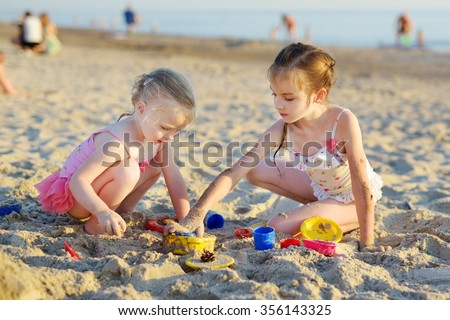Two little sisters having fun on a sandy beach - stock photo