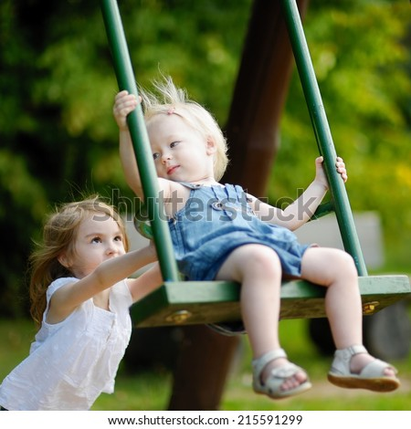 Two little sisters having fun on a swing on summer day - stock photo