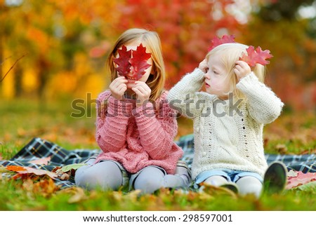 Two little sisters having fun together in beautiful autumn park on a sunny day - stock photo