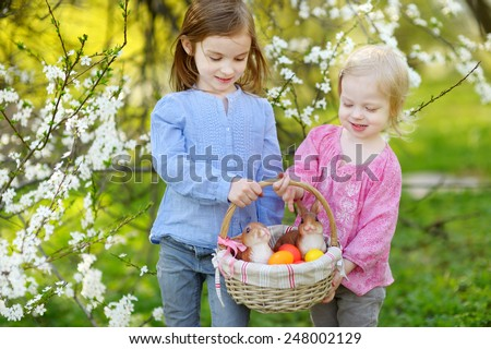 Two little sisters holding a basket of Easter eggs in blooming spring garden on Easter day - stock photo
