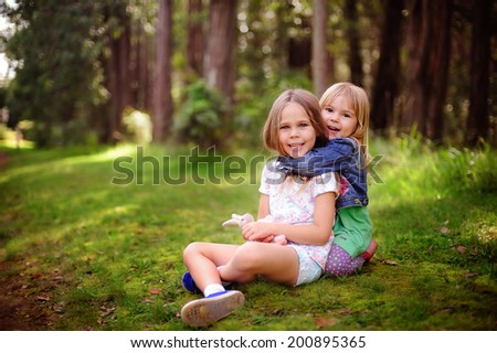 two little sisters hugging outdoor
