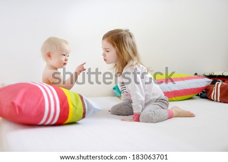 Two little sisters in bed on sunny morning - stock photo