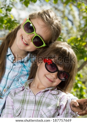 Two little sisters in sunglasses posing outdoor