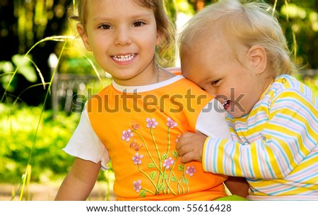 Two little sisters laugh and played against summer nature.