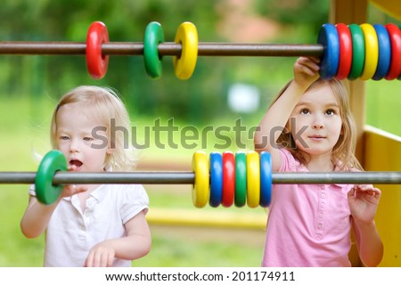 Two little sisters learning to count at a playground - stock photo