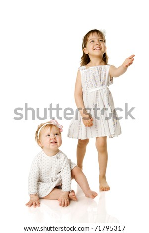 Two little Sisters looking up with interest isolated on white - stock photo