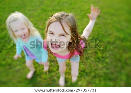 Two little sisters making funny faces outdoors - stock photo