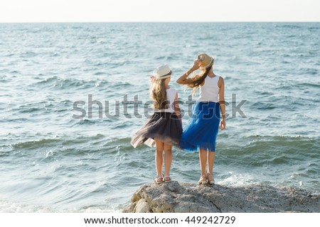 Two little sisters on the rocky shores of the Black Sea - stock photo