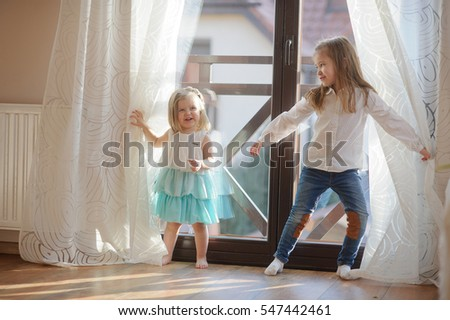 Two little sisters play in the room. Girls hide behind curtains, and then joyfully jump out because of curtains.