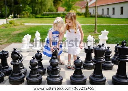 Two little sisters playing giant chess outdoors - stock photo