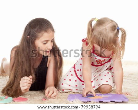 two little sisters playing on a carpet - stock photo