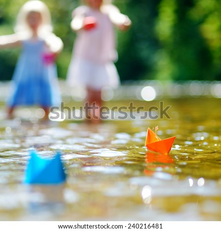 Two little sisters playing with paper boats by a river on warm and sunny summer day - stock photo