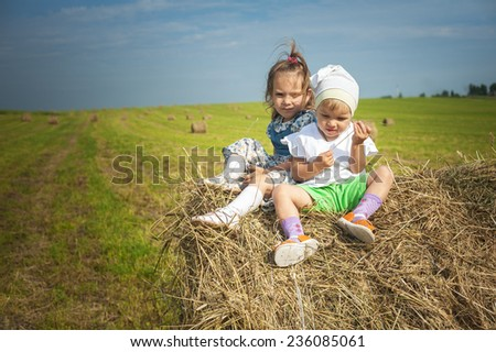Two little sisters sits on haystack. - stock photo