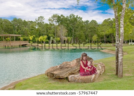 Two little sisters sitting on a large rock with pretty lack in background. - stock photo