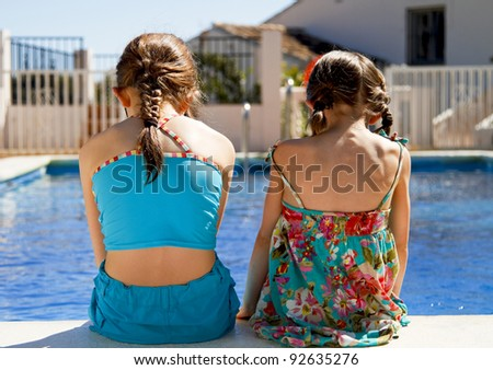 Two little sisters sitting side by side on the pool edge - stock photo