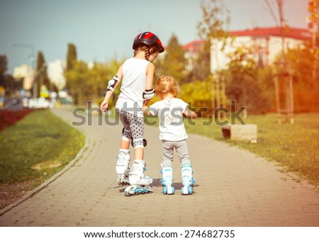 two little sisters to roller skate on the street, back view - stock photo
